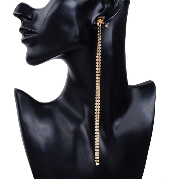 Mannequin wearing long gold tone zipper style earrings