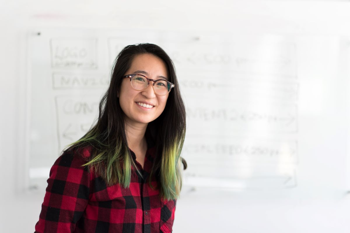 a smiling education worker standing in front of a whiteboard