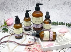 A product image of the skin care line for normal to dry skin surrounded by a rose, a white and a purple string of pearls and a sprig of eucalyptus.