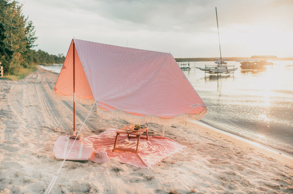 pink beach tent on the sand next to the water