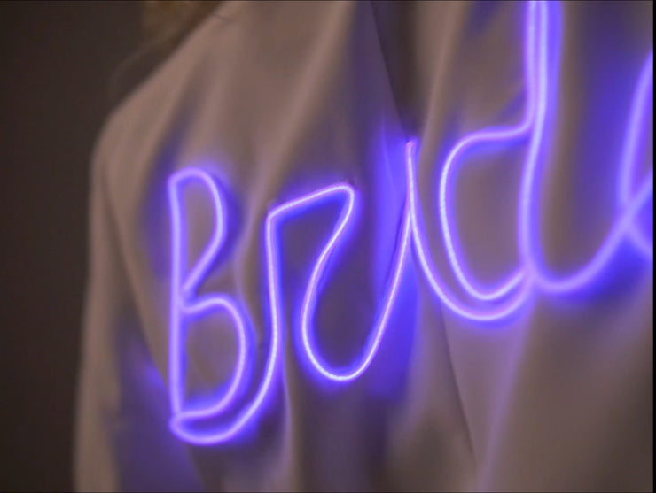 Closeup of light up bride text on a white bridal jacket