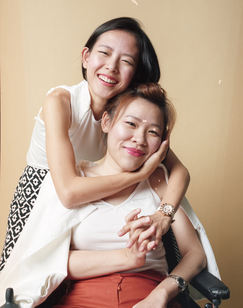 Elisa embracing Yean Cheng from the back as they smile into the camera