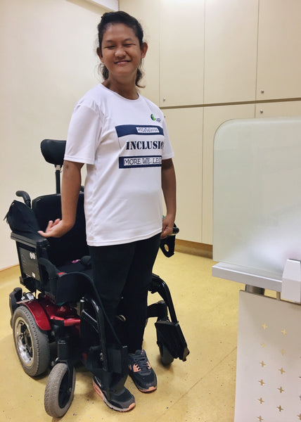 Syafiqah standing by her wheelchair in sporty attire