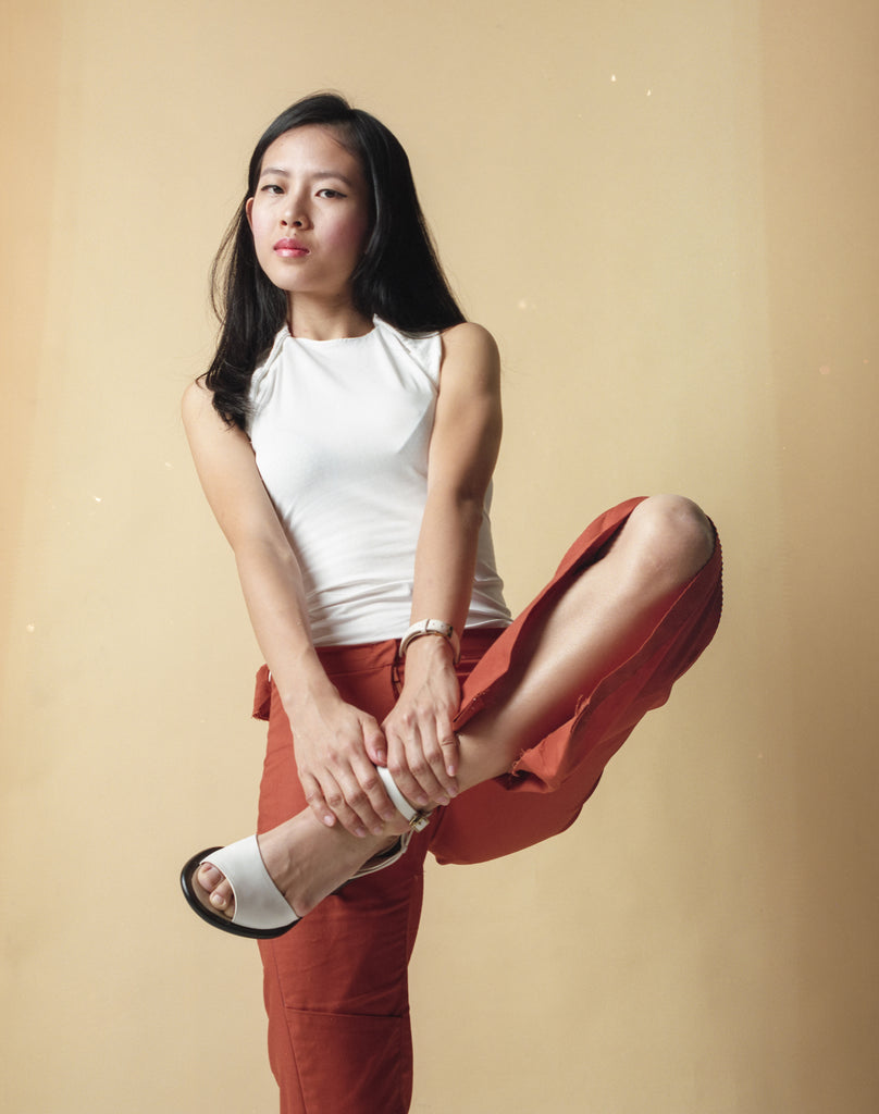 Elisa dressed in Gene Ave's sleeveless white top and long orange pants. She is posing with both hands holding her leg up by the ankles while balancing on the other leg..