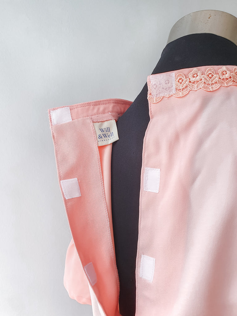 Multiple Velcro attachments at the back of the pink blouse. Will & Well label visible on the inside of the blouse.