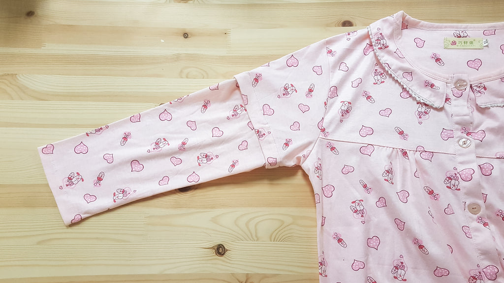 Partial view of pink pyjama top with pink hearts and cartoon dog prints. It is laid on a flat wooden surface and the main focus is the detachable long sleeves.