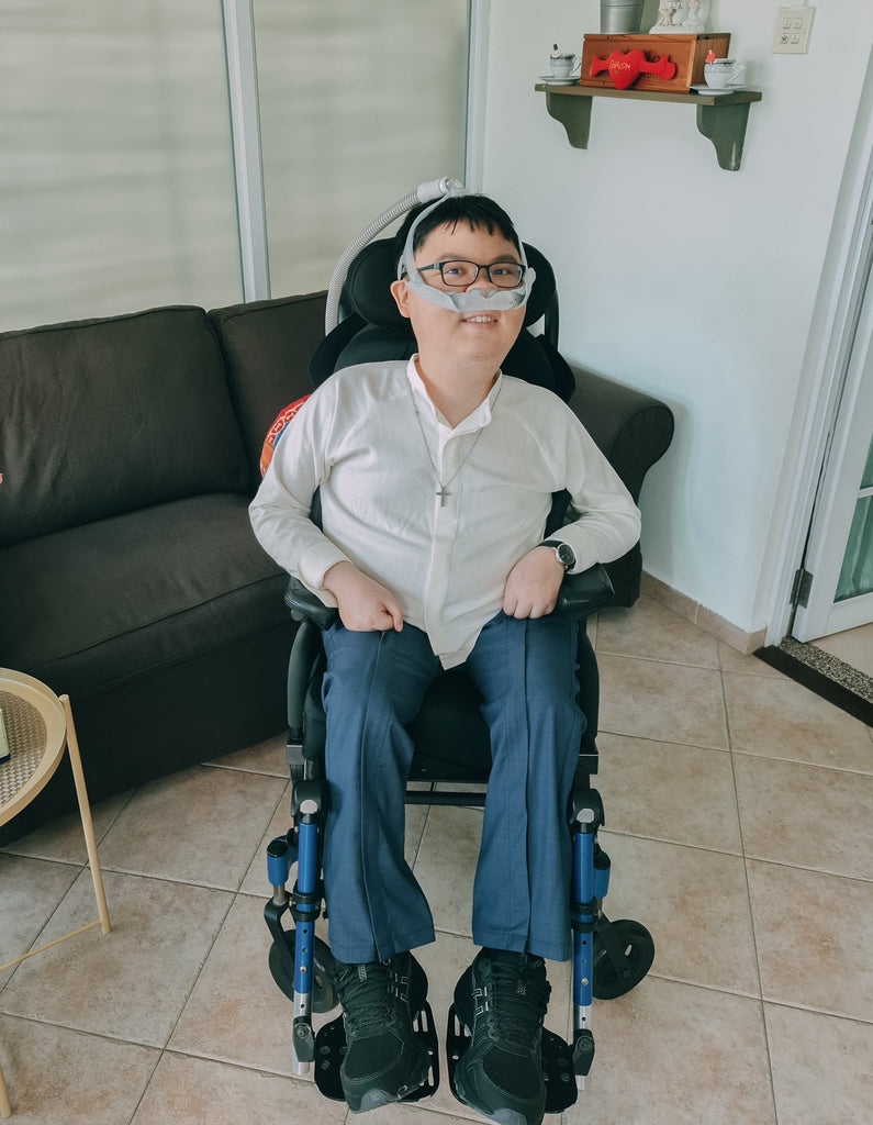 Shalom, a young man, seated in a wheelchair dressed in a customised white shirt and blue long pants