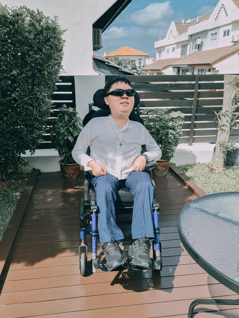 Shalom, a young man, seated outdorrs in his wheelchair while wearing a customised white shirt and blue long pants. He completes the look with a stylish pair of sunglasses.