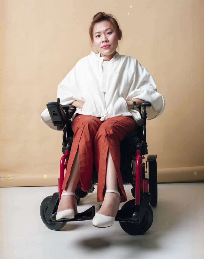 Yean Cheng seated in her wheelchair. She is wearing long orange pants and textured white cape from the Gene Ave collection.
