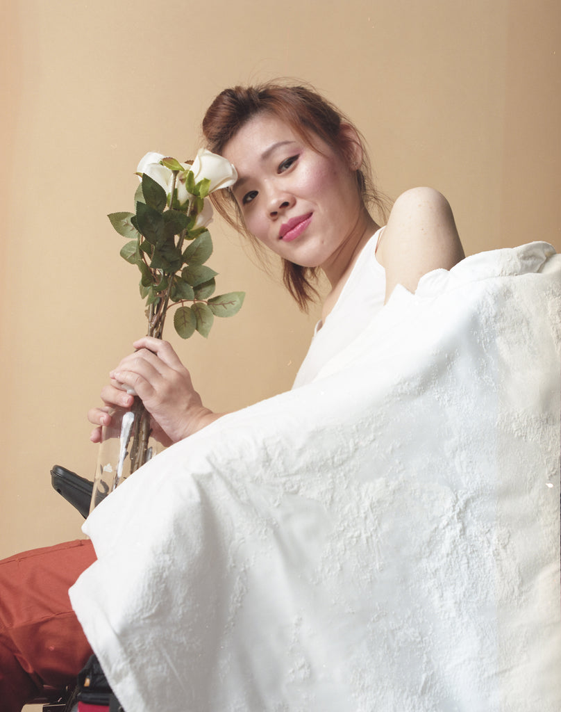 Yean Cheng holding a few stalks of white roses toward her face as she smiles to the camera. In front of her is a textured white cape from the Gene Ave collection.