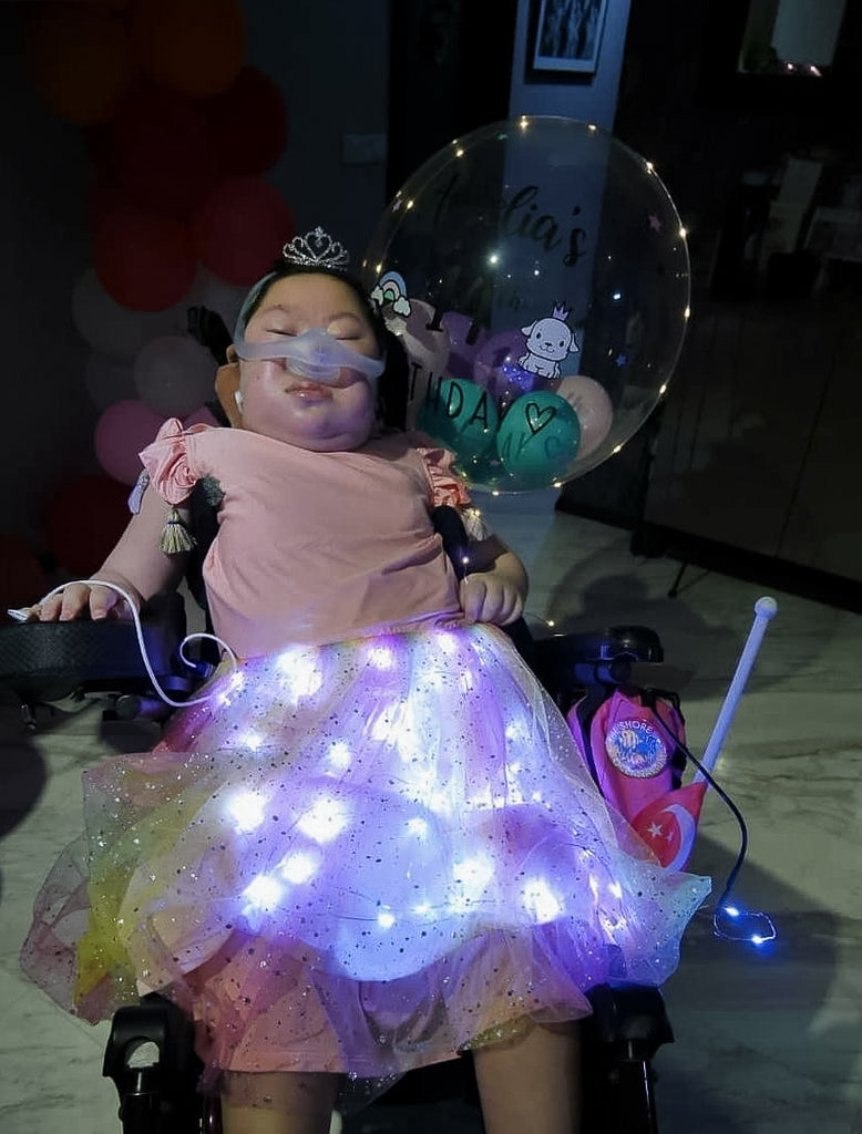 Amelia seated in a wheelchair and wearing her pink dress with lighted up skirt. a 14th birthday balloon is next to her.