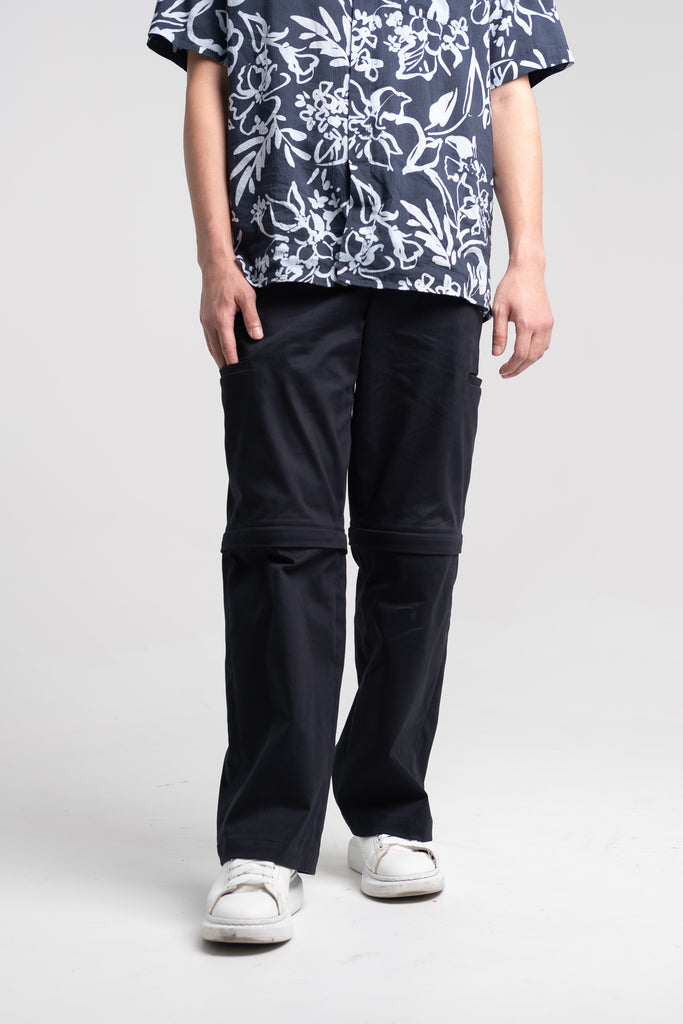 The Convertible Cargo Pants in Black, being worn as its long pants version.