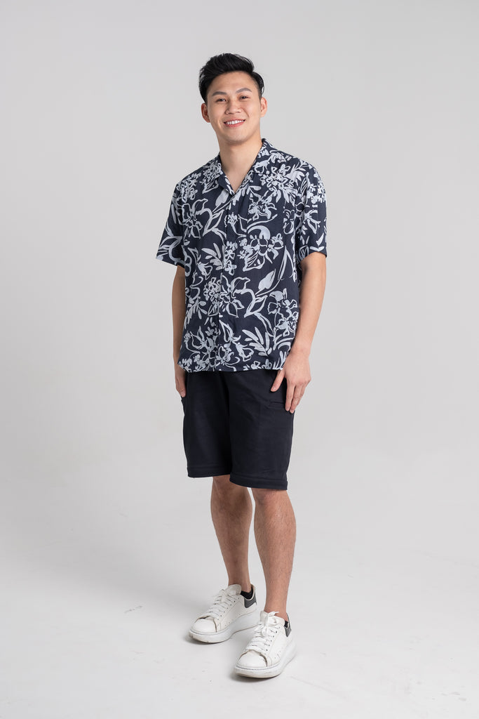 Gavin, a young Chinese man, wearing the Tropical Short Sleeve Shirt in Navy and Convertible Cargo Pants in Black. The Cargo Pants has been transformed into a pair of shorts.