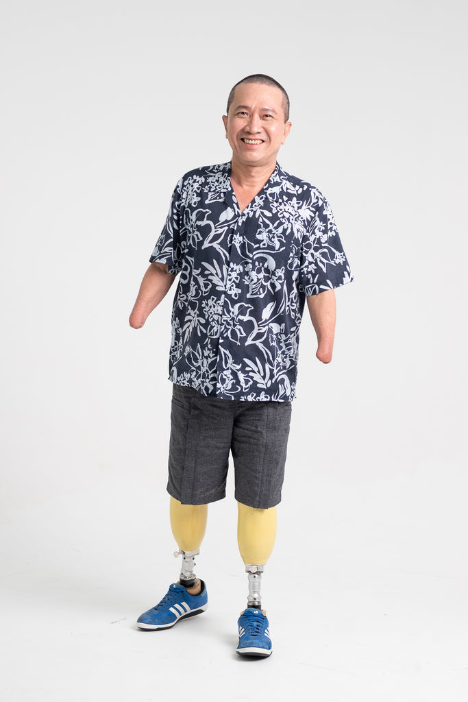 Whee Boon, a 4-limb amputee, smiling at the camera as he donned the Tropical Short Sleeve Shirt in Navy and Unisex Adjustable Shorts in Shadow Grey.