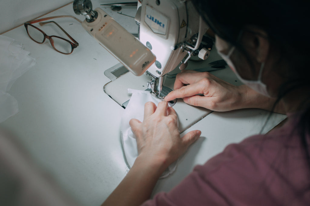 Close up of seamstress working on a face mask with a sewing machine.
