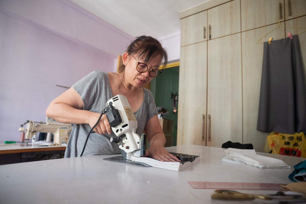 A Chinese lady bending over the table and using an electronic cutter to cut a stack of white fabric at her workstation.