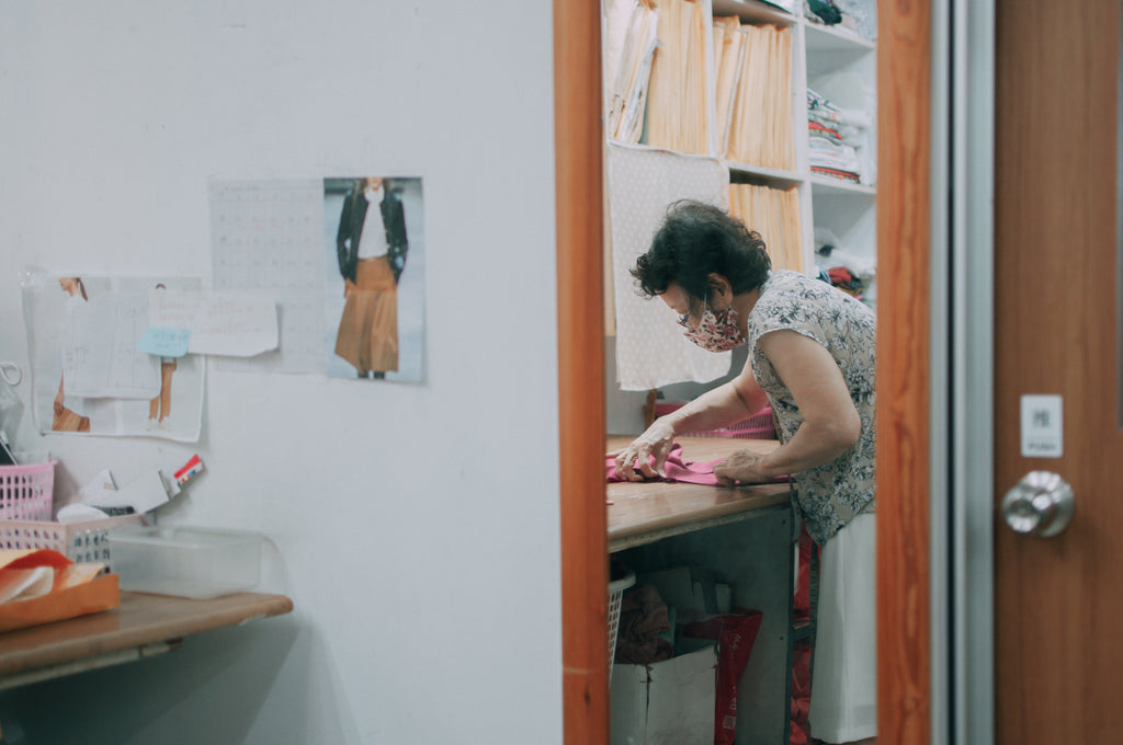 A reflection of an elderly lady in a mirror, hunched over a table as she works on dressmaking.