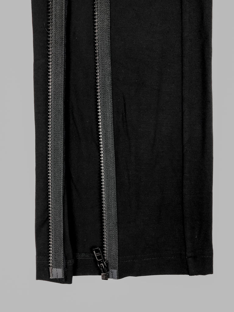 Close up of the bottom of customised pants in black. Parallel FrontSlit opening on both sidesallow pants to open fully.