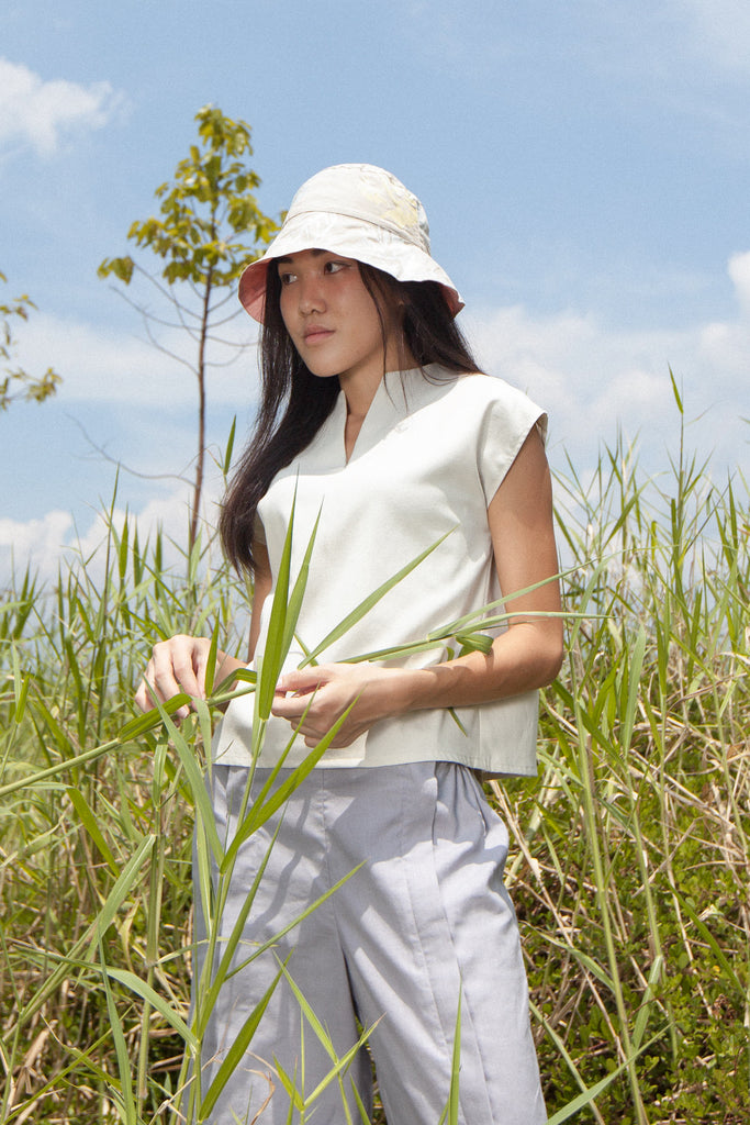 Alexis posing in the midst of tall grass, wearing the two-Way Blouse in Ivory and Unisex Adjustable Pants in Heather Blue.