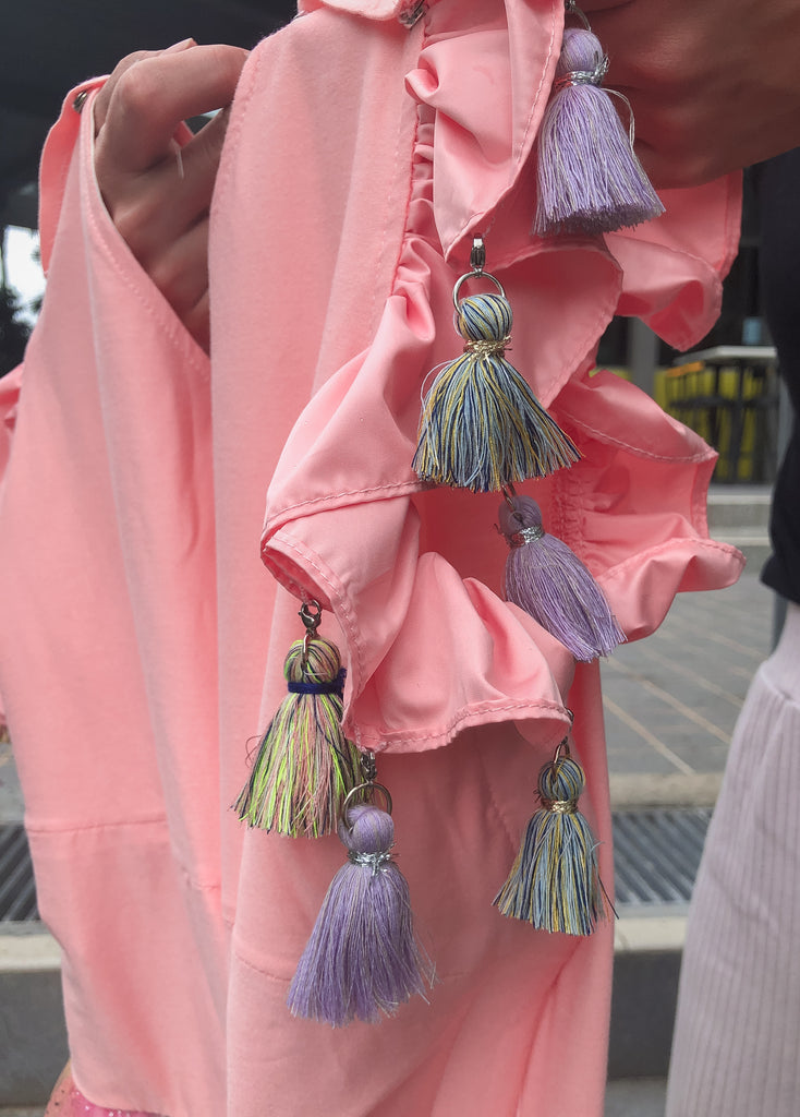 Colourful tassles with mini hooks dangles from the sleeves of the dress around the shoulder.