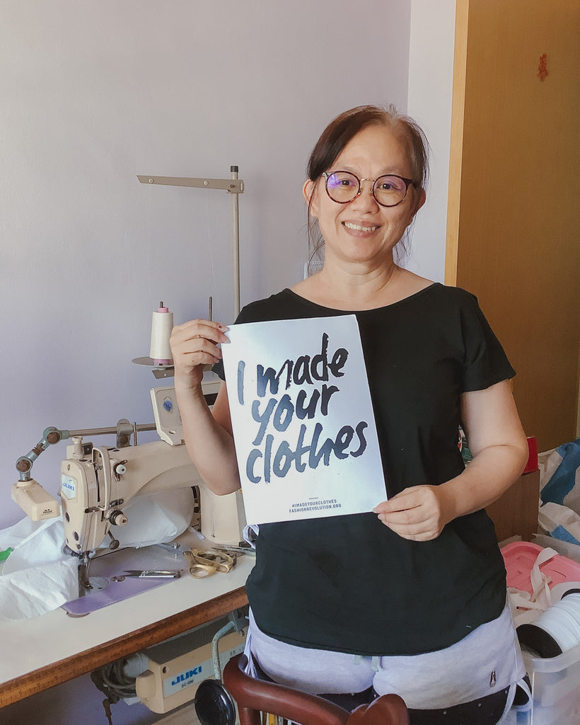 """A Chinese lady in her 50's holding up a white A4 sized paper with the text """"I made your clothes"""". She is standing in front of her workstation with a sewing machine in the background."""