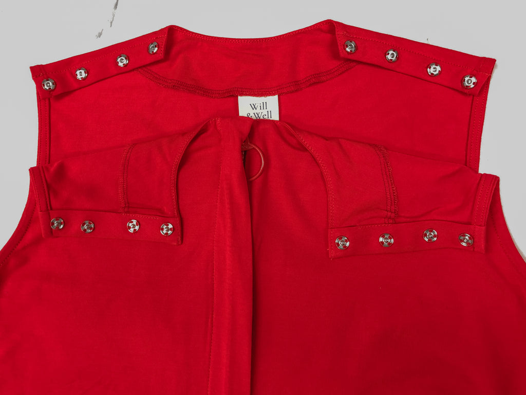 Close up of the customised Sleeveless Blouse in bright red. Snap buttons on the shoulders to facilitate easy dressing processes.