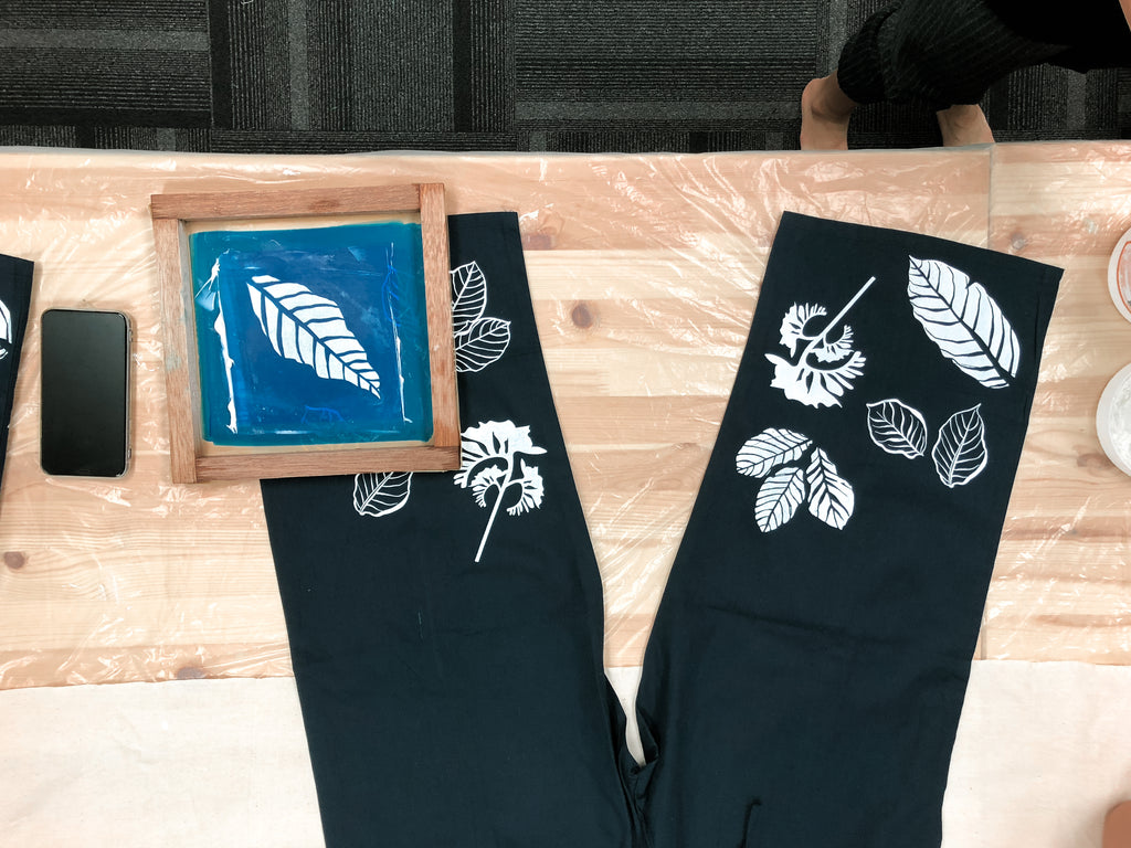 A flat-lay shot of the silkscreen board on the Navy Blue Unisex Drawstring Pants