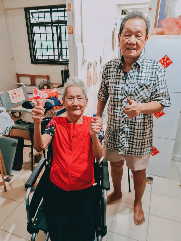Mdm Tiah in her wheelchair and her boyfriend standing next to her, showing a thumbs-up after putting on the customised garments.