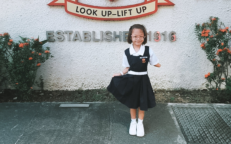 Youngest client, Chrislyn, with a big smile in her redesigned school uniform