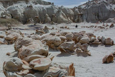One figure sitting in the distance on a sandy cliff face, with several rocks in the foreground.