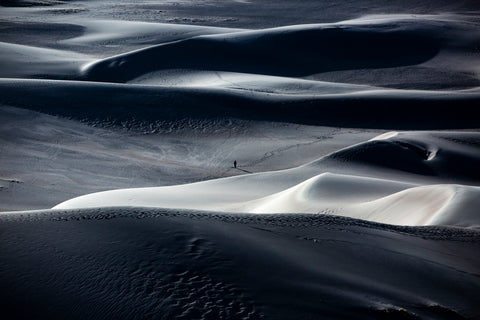 One figure in the center of surrounding sand dunes that are in shadow.