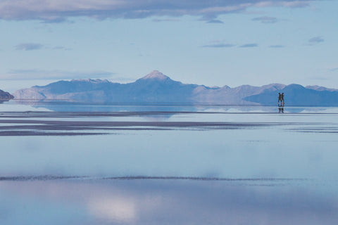 Two figures back to back in front of mountains. A purple hue to the photo.