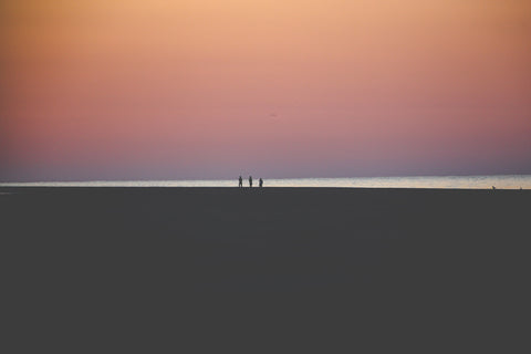 three small figures on a grey beach with purple and orange sunset in the background