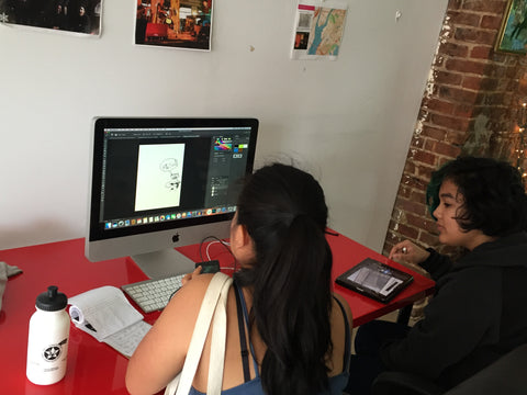 Two young women of color draft graphic design on a desktop computer.