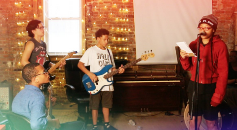 Four young students of color play music - one sings at a microphone, one plays bass, one plays guitar, and one listens