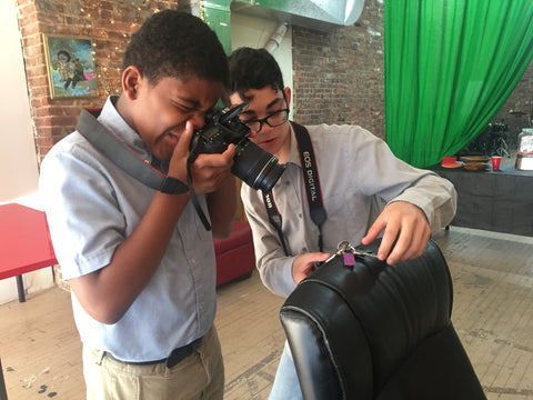 Two students of color doing photography - one holds a camera and the other stages a small scene on the back of a chair.