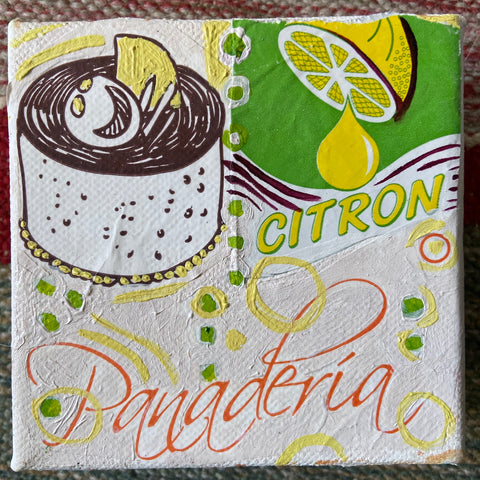 "white canvas square painted with lemon on green background in top right corner and cartoon figure swimming in pot of lemons reads ""Citron"" on top right and ""Panaderia"" in curly font across bottom"