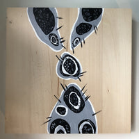 Abstract tube shapes in gray and black and white on a wood panel.