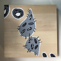 Abstract tubular shapes in gray and black with white on a wood panel.
