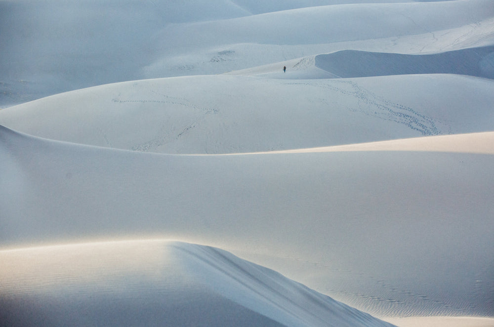 A photo of a person on the great sand Dunes in Colorado at sunrise.