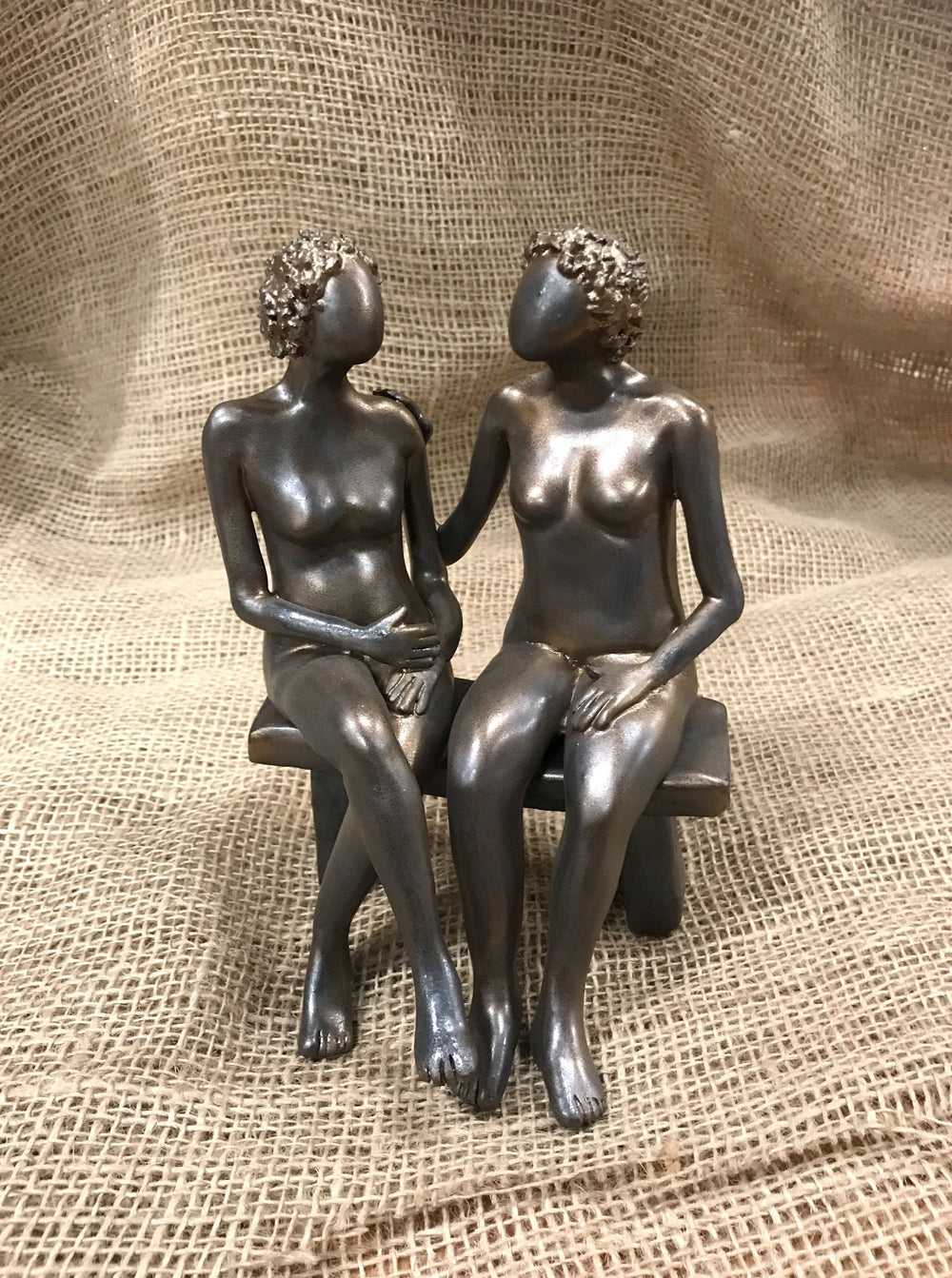 Two women sitting on a bench painted in bronze coloring, made of clay.