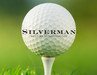 Siverman logo on large golf ball in front of green glass