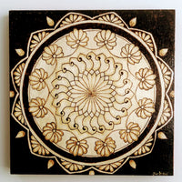 A mandala pattern burned into a piece of wood.