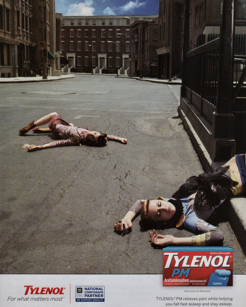 Two people lying in the street with buildings behind.