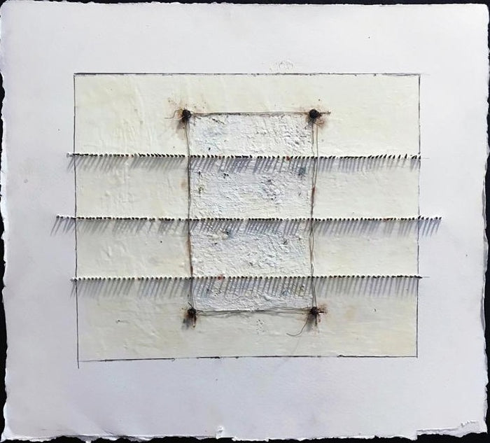 White paper in a square with a wax with rusted nails going across in three rows over a larger rectangle.