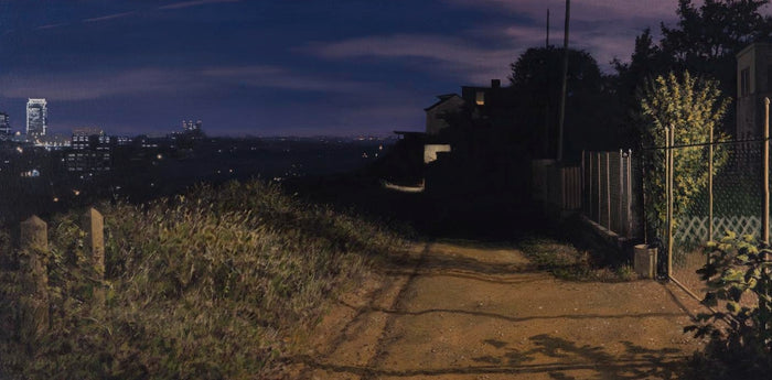 A dirt road leading into darkness with the New York skyline in the distance.