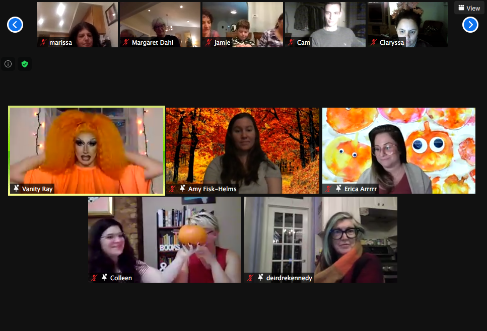 "Zoom screen featuring drag queen Vanity Ray in an orange outfit with a large orange wig with 4 other people on the main screen showing off their decorations for the ""Autumn Colors"" theme (including Fall/Pumpkin backgrounds as well as someone holding a pumpkin). Above them, 5 other participants look on."