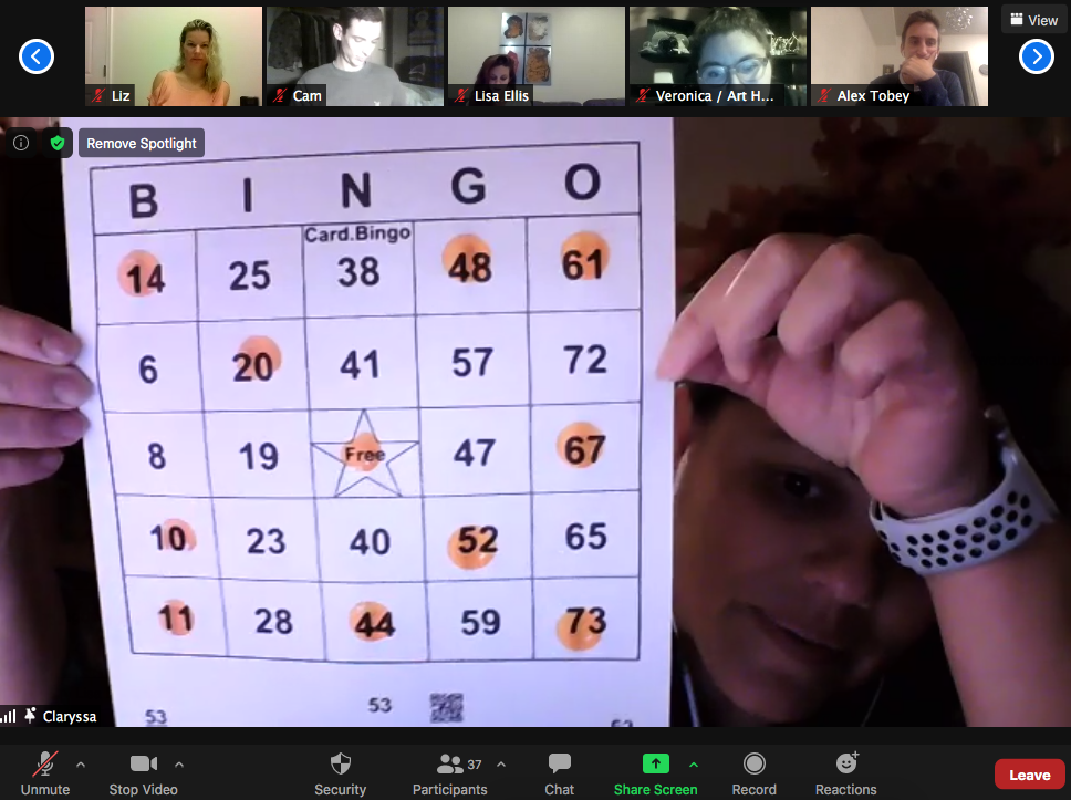 Zoom screen featuring a participant holding up their winning Bingo board, as 5 other people on the top row look on.