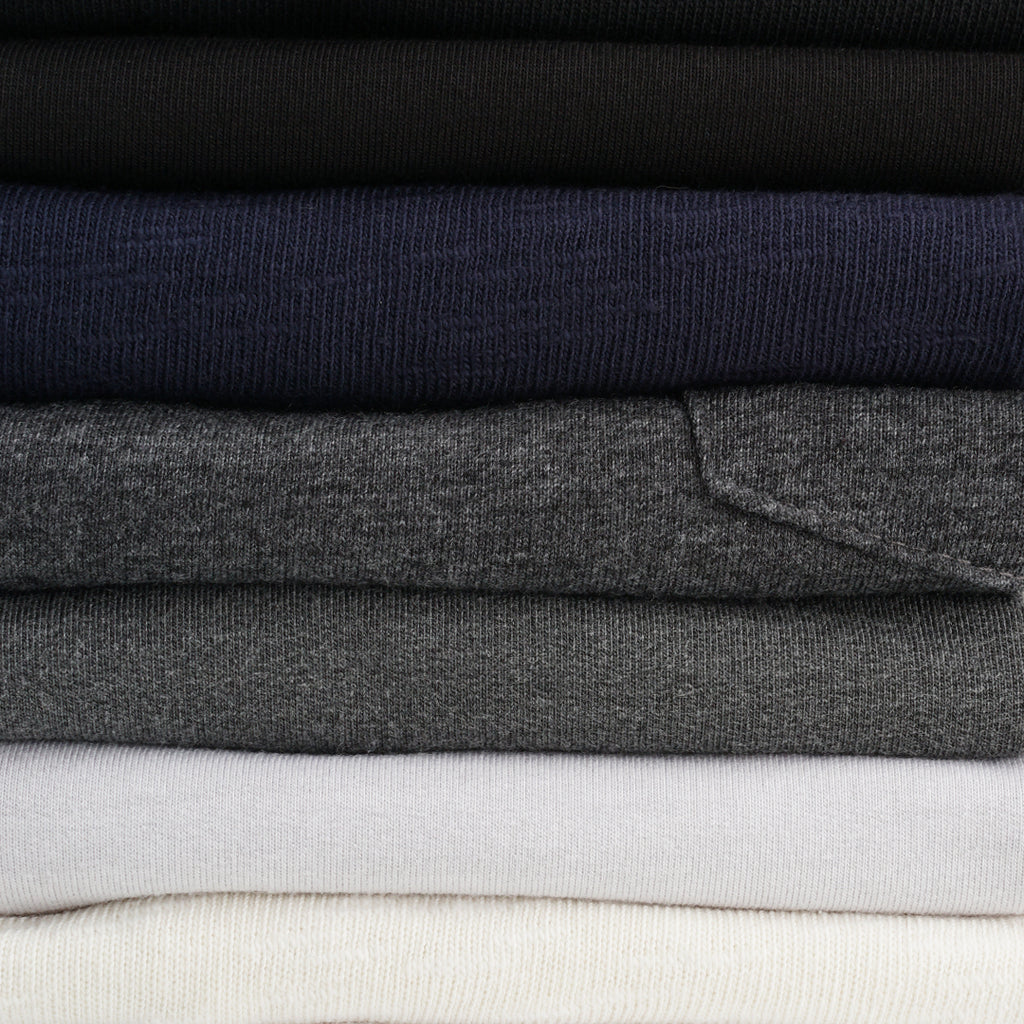 Stack of men's premium basic t-shirts.  Black, navy, charcoal, grey, & ivory