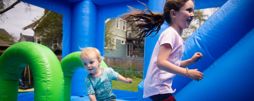 Girl and boy jumping on bouncy castle in Victoria, BC